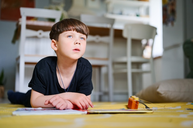 Preschool blanke jongen liggend op de vloer thuis, boeken lezen en kijken naar foto's. home onderwijs concept