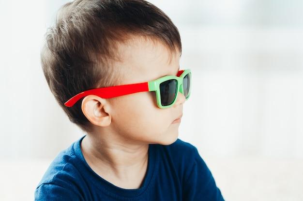 Preschool jongen in groene zonnebril, modieus en stijlvol