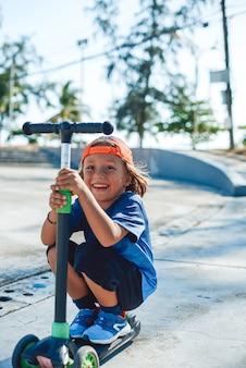 Preschool jongen met baseballpet gekleed in casual kleding glimlacht en geniet van zijn hobby rijden op scooter. extreme sporten en kinderen.