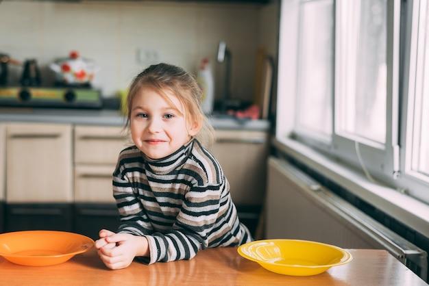 Preschool meisje aan de tafel in de keuken met lege borden