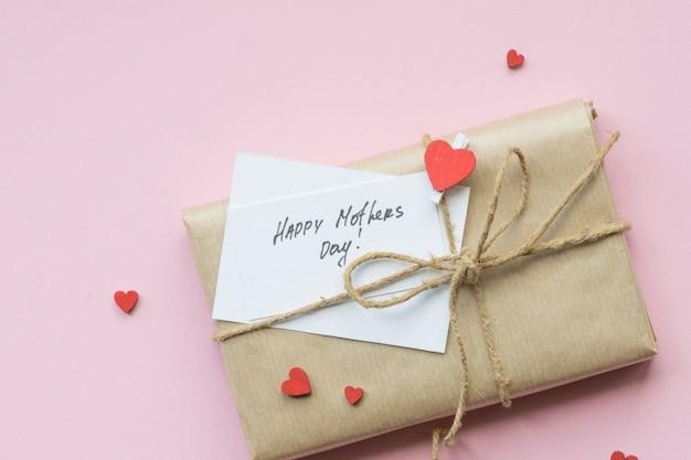 Present verpakt in bruin ambachtelijk papier en stropdas hennepstreng. geschenkdoos met groeten op moederdag. bovenaanzicht