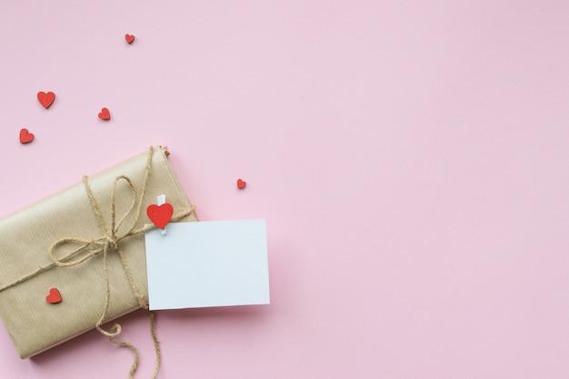 Present verpakt in bruin ambachtelijk papier en stropdas hennepstreng. romantisch cadeau met decoratieve rode harten. bovenaanzicht