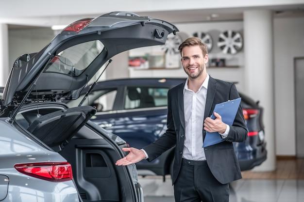 Presentatie. glimlachende man in donker pak en wit overhemd met map wijzend op open kofferbak van auto die in autodealer staat