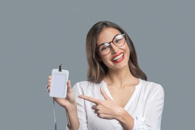 Presentatie. mooie vrolijke jonge succesvolle vrouw in glazen wijzend met vinger op badge binnenshuis