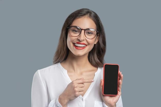 Presentatie, smartphone. mooie vrolijke jonge succesvolle vrouw in glazen wijzend met vinger naar smartphone binnenshuis