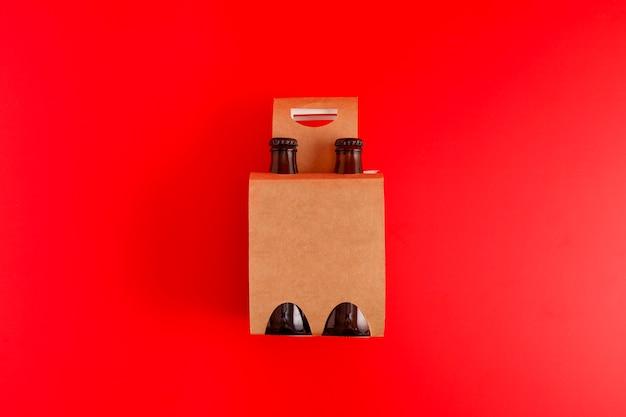 Presentatie van een pakket van vier bieren met rode achtergrond