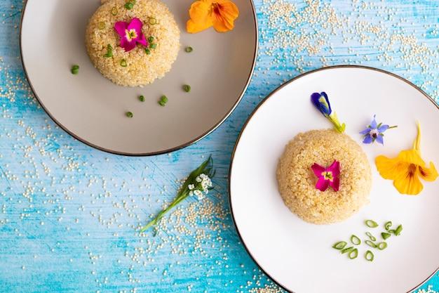 Presentatie van een quinoa bord versierd met eetbare bloemen