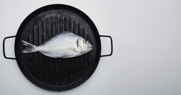 Presentatie van verse wilde zeebrasem op grillpan klaar om te koken