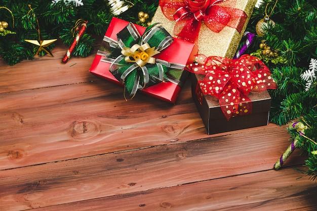 Presenteer geschenkdozen met kleurrijk lint op hout achtergrond met kerstboom en traditionele ornamenten xmas rekwisieten met kopie ruimte. concept van gelukkig en vreugdevol in festival.
