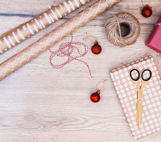 Presenteer in wrap in de buurt van kerstballen, wendingen en scharen