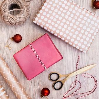 Presenteert in wraps dichtbij kerstmisballen, draden en schaar