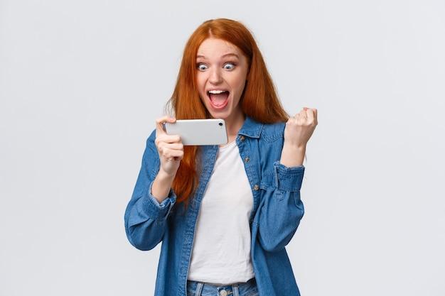 Prestatie, doel en succes concept. vrolijke gelukkige schattige roodharige tienermeisje vuist pomp triomfeert, starend naar smartphone display verbaasd en tevreden, winnende speluitdaging