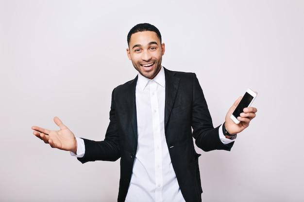 Prestatie geweldige resultaten op het werk, succes in de carrière van knappe jongeman in wit overhemd, zwarte jas die geluk uitdrukt. stijlvolle zakenman, vreugde, glimlachen, positiviteit.
