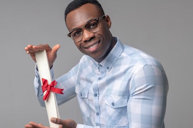 Prestatie, plezier. gelukkig succesvolle donkere man met bril met belangrijke scroll in zijn handen in uitstekende bui