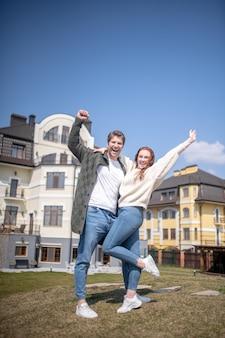 Prestatie, verrukking. vrolijke knuffelende jonge volwassen man en vrouw die triomfantelijk hun handen opsteken terwijl ze buiten staan tegen de achtergrond van nieuwe huizen
