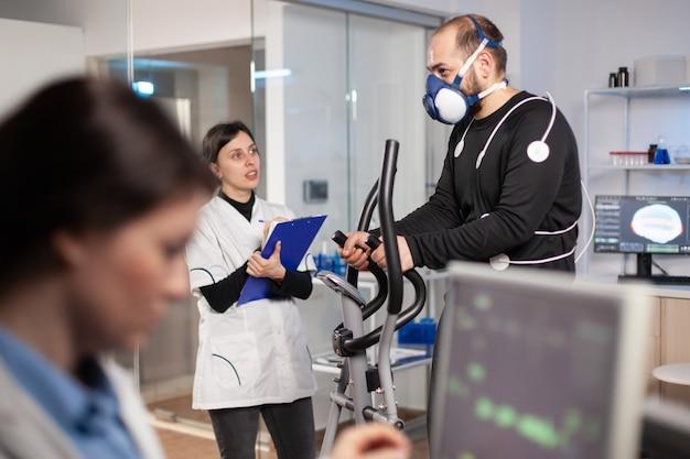 Prestatieatleet die in laboratoriumwetenschap loopt en het uithoudingsvermogen test met masker en elektroden, biomechanica-sensoren. cardio-onderzoek. trainingssensoren die fitness meten.