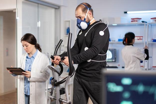 Prestatieatleet die op crosstrainer loopt met elektroden bevestigd op lichaam en masker in testlaboratorium, wetenschapper arts die de hartslag bewaakt en naar tablet-pc kijkt.