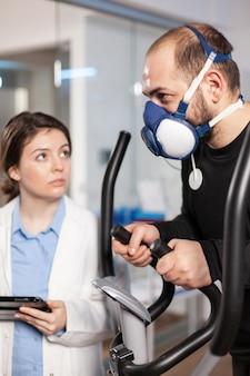 Prestatieatleet met bevestigde elektroden die op een crosstraining loopt met een masker en de hartslag test. analyse van biomechanica bij muscualaire oefeningen.