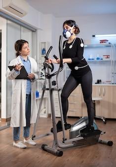 Prestatiewetenschapper die biomechanica van atleetloper op crosstrainer onderzoekt. team van onderzoekers die het uithoudingsvermogen, vo2 max, psychologische weerstand monitoren.