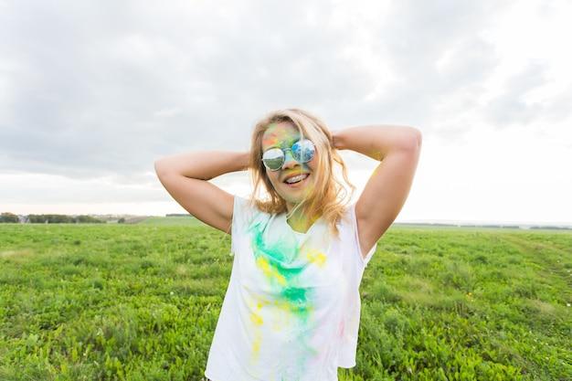 Pret, gelukkig, mensen en vakantieconcept - jonge vrolijke vrouw bij holi-verfpartij