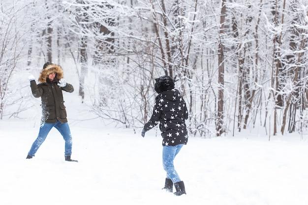 Pret-, seizoen- en vrijetijdsconcept - liefdespaar speelt winterhout op sneeuw