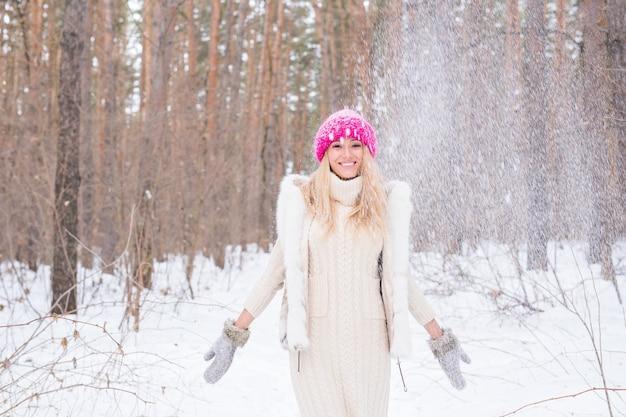 Pret, winter en mensenconcept - aantrekkelijke vrouw gekleed in witte jas die sneeuw werpt.