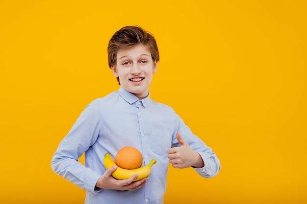 Preteen aardige jongen met fruit in de hand, banaan en sinaasappel, in het blauwe shirt, geïsoleerd op gele muur