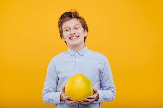 Preteen gelukkige jongen met pompelmoes fruit in de hand, in het blauwe shirt, geïsoleerd op gele muur