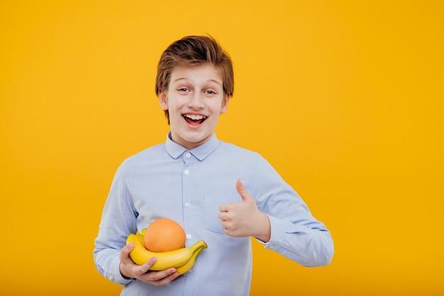 Preteen glimlachende jongen met fruit in de hand, banaan en sinaasappel, duim omhoog, in het blauwe shirt, geïsoleerd op gele muur