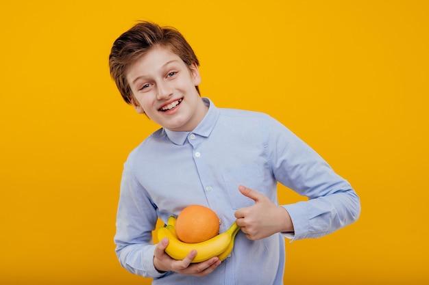 Preteen hapy jongen met fruit in de hand, banaan en sinaasappel, in het blauwe shirt, geïsoleerd op gele muur