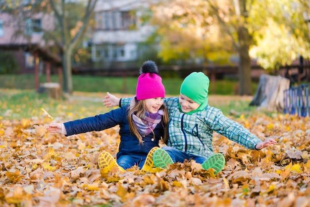 Preteen jongen en meisje spelen met geel gebladerte