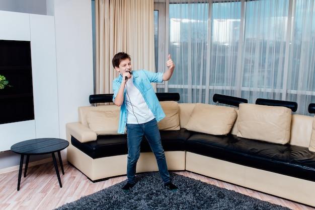 Preteen jongen zingen met microfoon in de huiskamer.