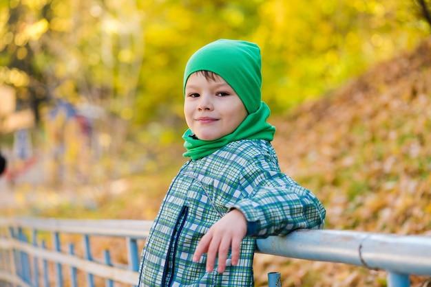 Preteen kind in groene hoed en jas buitenshuis