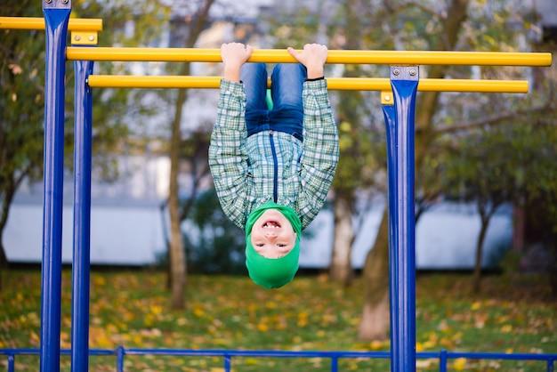 Preteen kind in groene hoed op metalen staaf buitenshuis. schooljongen op horizontale balk ondersteboven