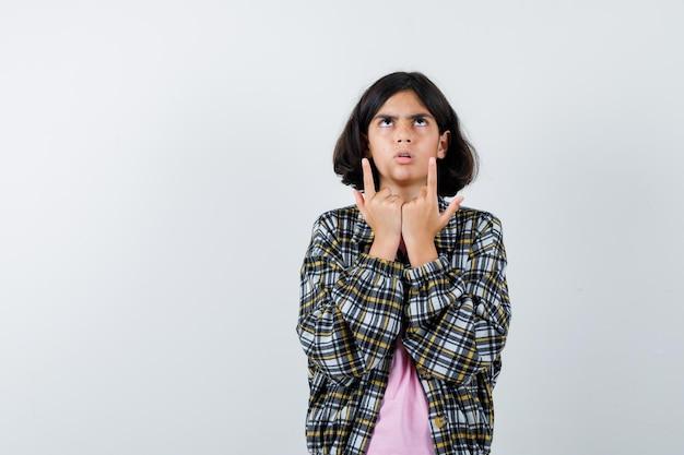 Preteen meisje dat omhoog wijst terwijl ze in shirt, jas denkt en er verloren uitziet, vooraanzicht.