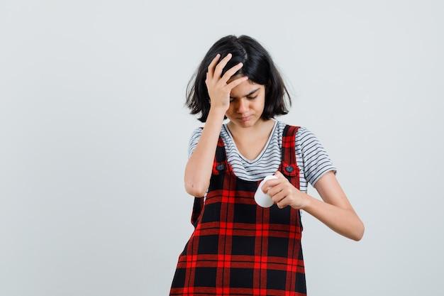 Preteen meisje hoofdpijn tijdens het kijken naar fles pillen in t-shirt, jumpsuit, vooraanzicht.