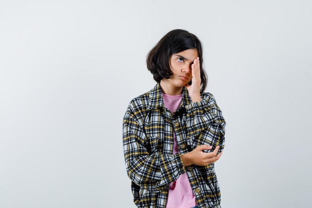 Preteen meisje houdt hand op oog in shirt, jas en kijkt verveeld. vooraanzicht.