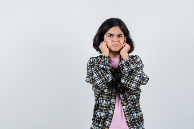 Preteen meisje houdt vuisten op haar kin in shirt, jas en kijkt ontevreden, vooraanzicht. ruimte voor tekst