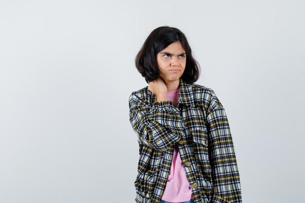 Preteen meisje in shirt, jas masseert haar nek terwijl ze opzij kijkt en er verontrust uitziet, vooraanzicht.