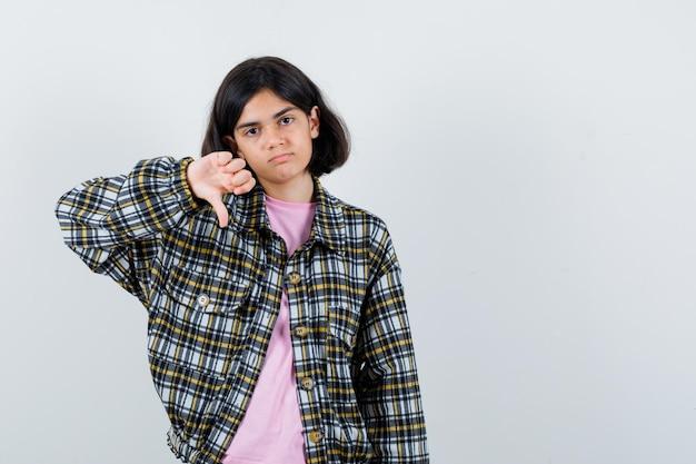 Preteen meisje in shirt, jas met duim naar beneden, vooraanzicht.