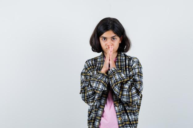Preteen meisje in shirt, jas met gecombineerde handen op de mond terwijl ze nieuws verwacht en er geduldig uitziet, vooraanzicht.