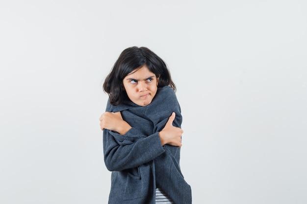 Preteen meisje in shirt, jasje knuffelen zichzelf en kijkt beledigd