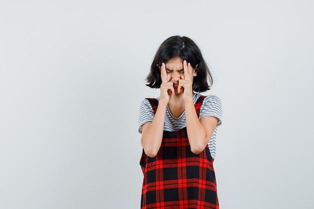 Preteen meisje in t-shirt, jumpsuit die haar gezicht knijpt en er stressvol uitziet