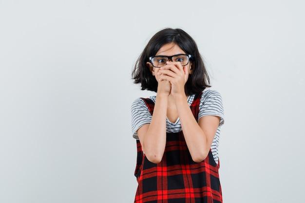 Preteen meisje met bril in t-shirt, jumpsuit en op zoek raar, vooraanzicht.