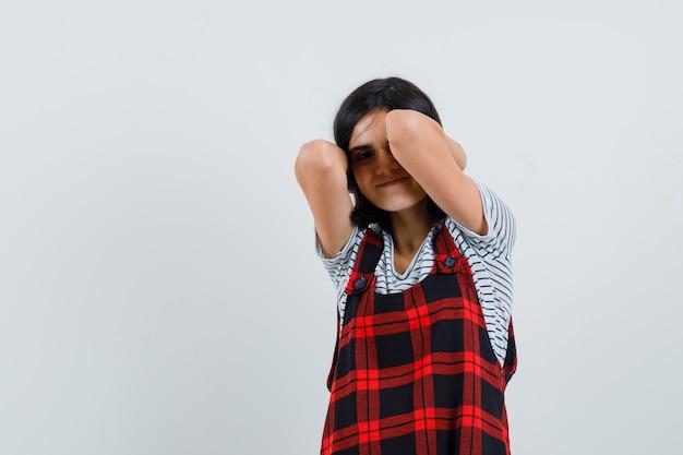 Preteen meisje met hand op haar nek in t-shirt