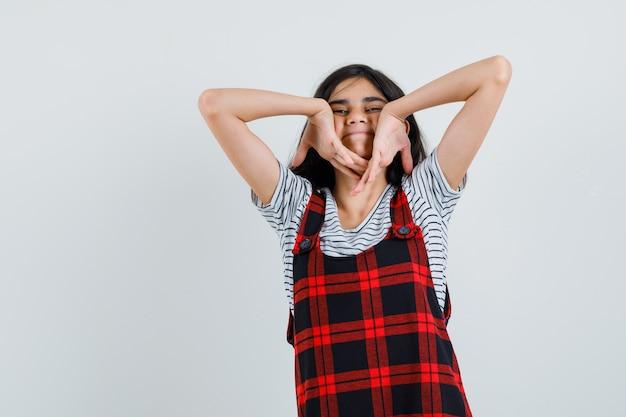 Preteen meisje met omgekeerde handen op haar gezicht in t-shirt