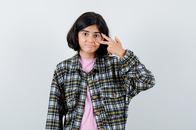Preteen meisje met v-teken over oog in shirt, jas vooraanzicht.
