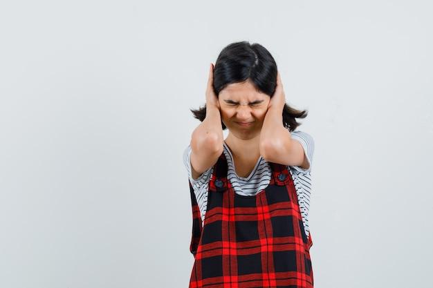 Preteen meisje omklemde hoofd met handen in t-shirt