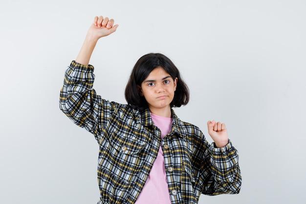 Preteen meisje strekt zich uit in shirt, jas en ziet er flexibel uit. vooraanzicht.