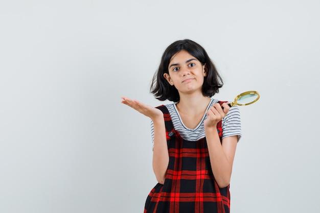 Preteen meisje toont hulpeloos gebaar terwijl vergrootglas in t-shirt, jumpsuit en op zoek verontrust.